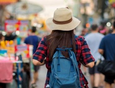 Tourist woman walking down a busy street new city