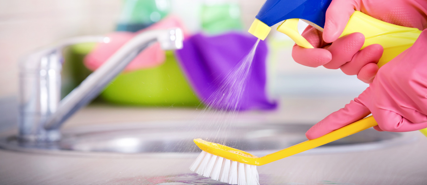 Person washing kitchen counter with scrubbing brush and spray cleaner