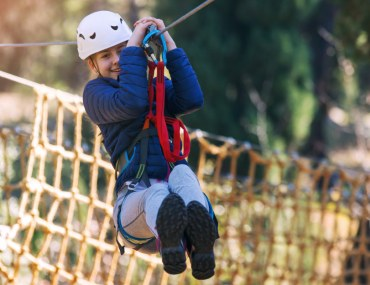 Girl enjoys zip lining activity sports club adventure park