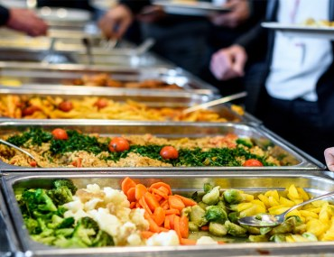 People taking food from a buffet spread