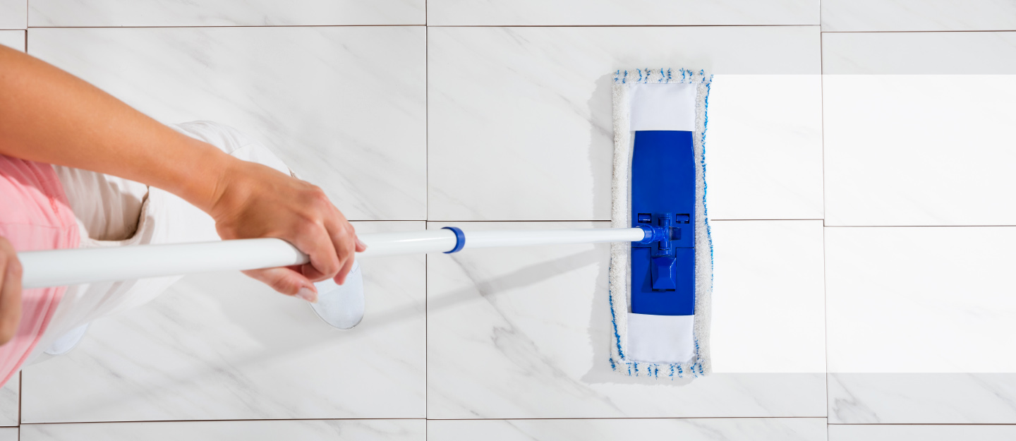 Person cleans floor tiles with mop