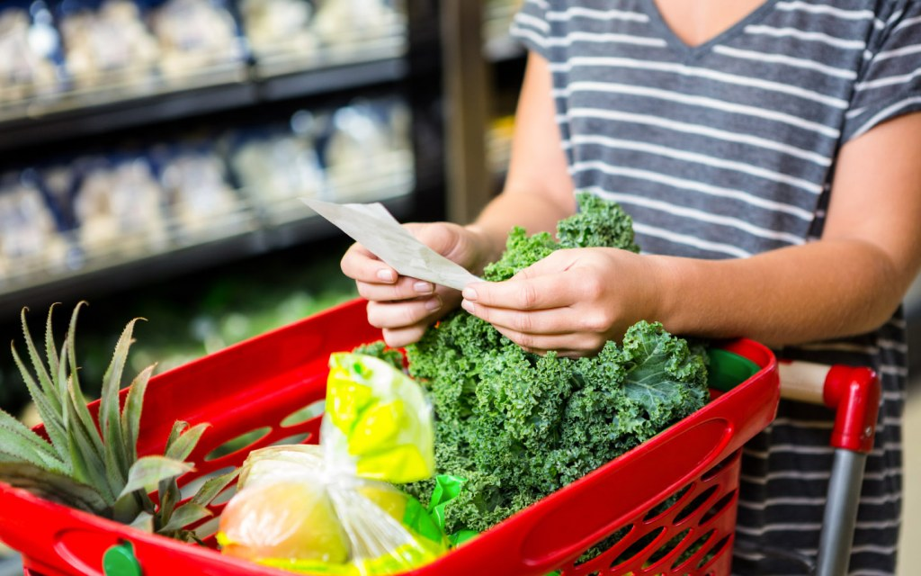 Woman reads list during grocery shopping
