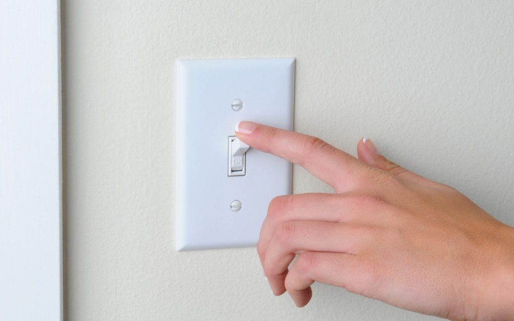 Woman flipping light switch