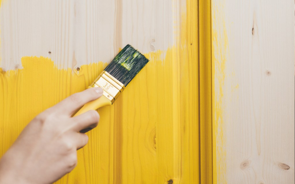 A woman paints wooden door with yellow paint