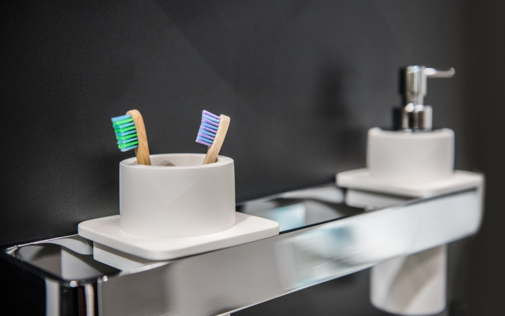 Toothbrush holder with two brushes and liquid soap dispenser