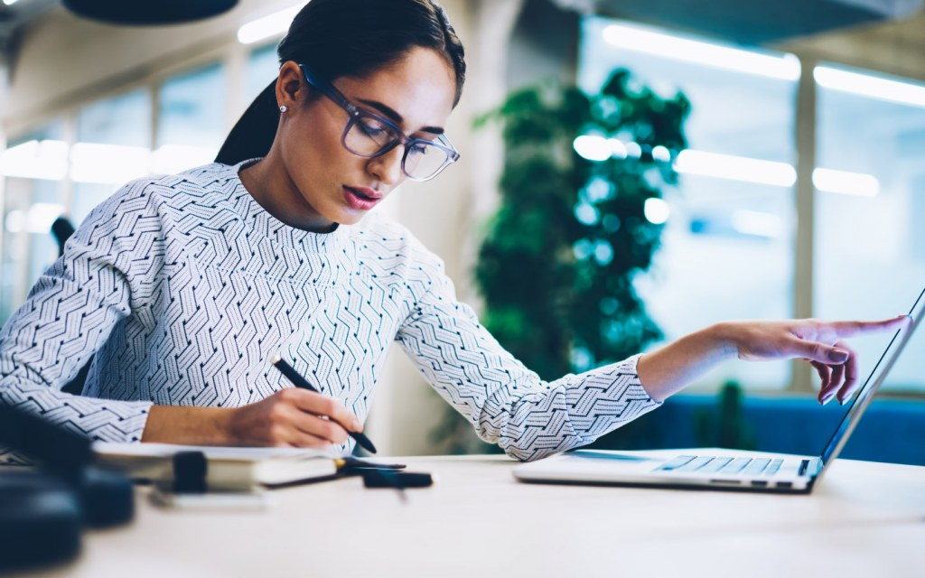 Woman notes down ideas on a notepad from her laptop