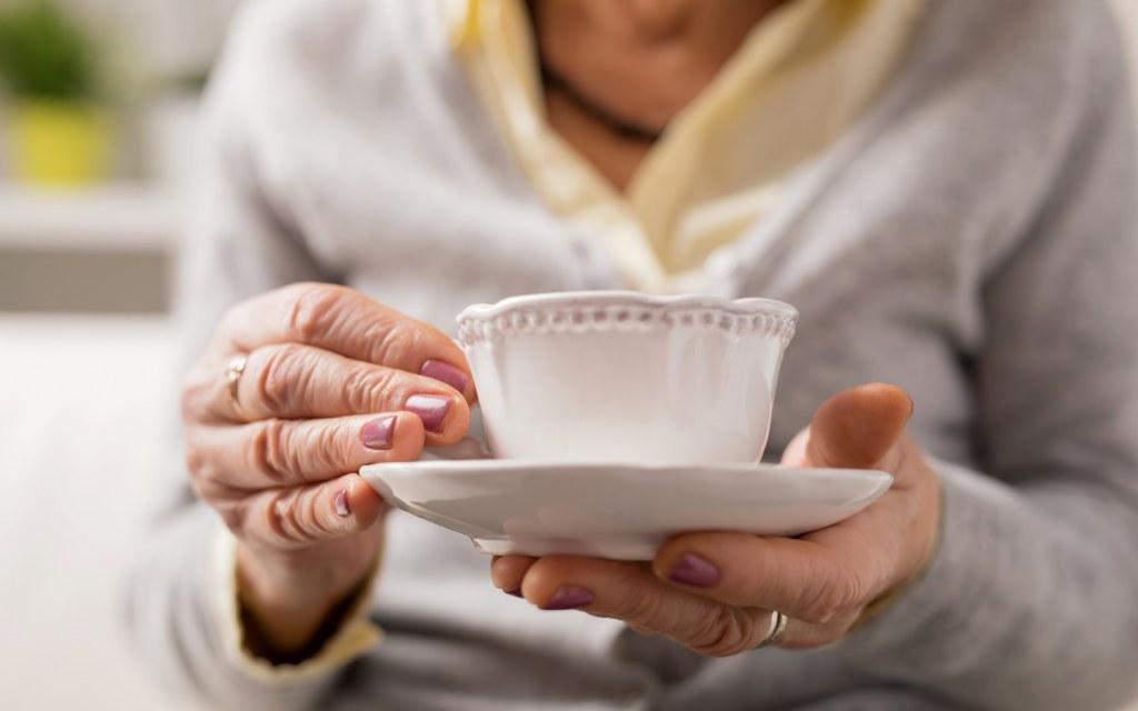 Elderly woman having a cup of tea or coffee