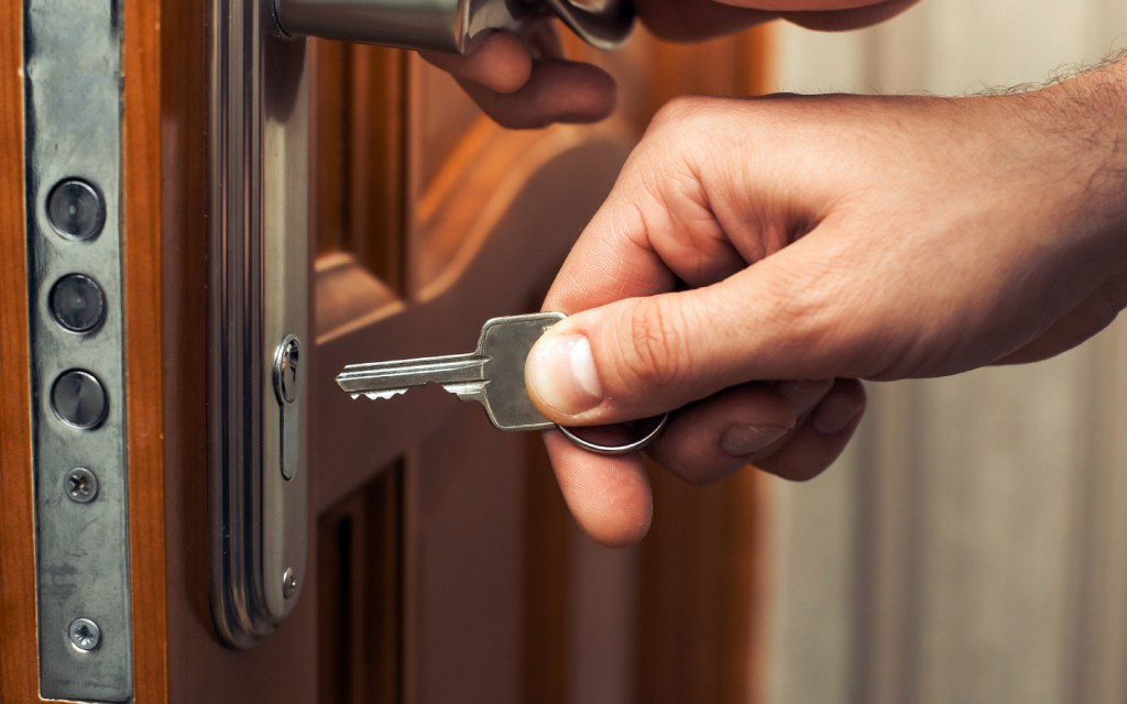 Person inserting key in door lock