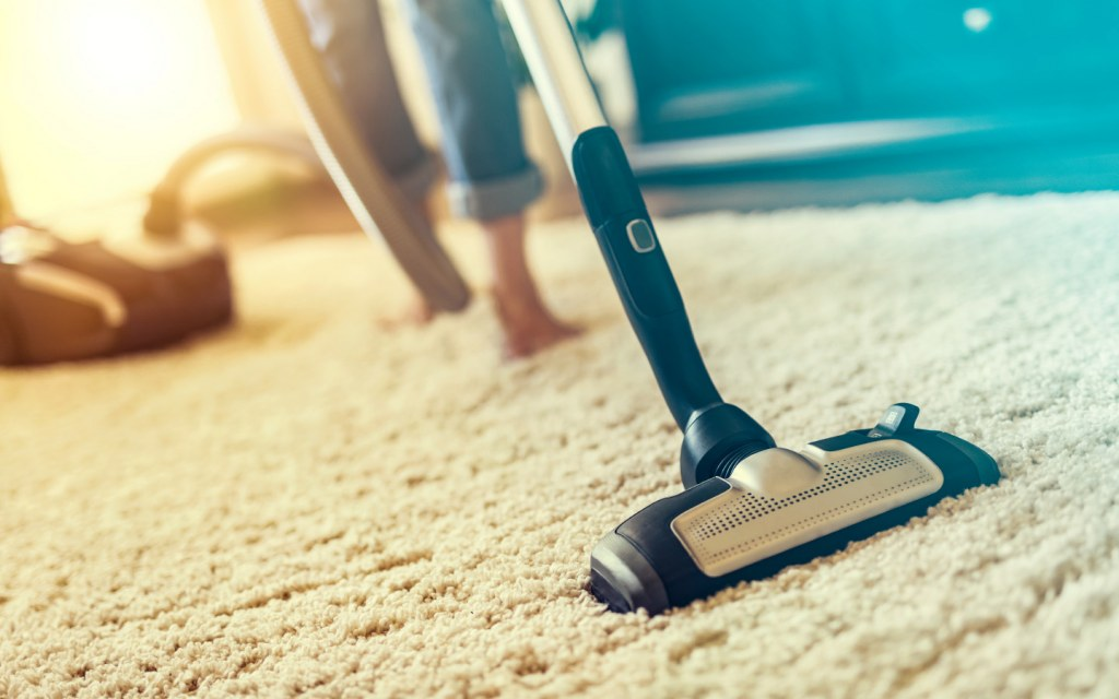 Person using vacuum cleaner on carpet rug