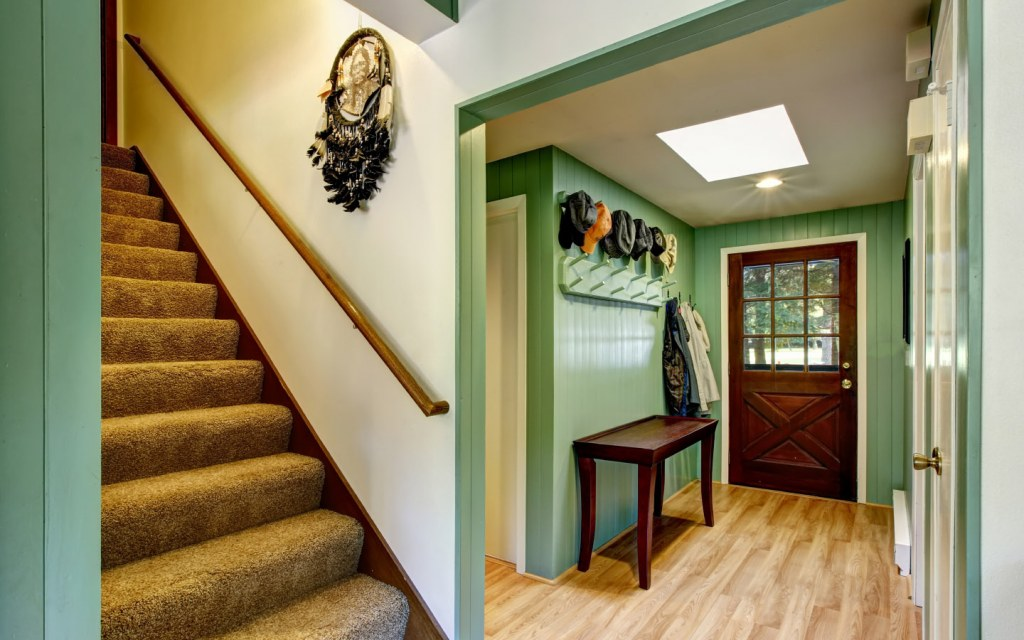 Green entryway with console table and skylight