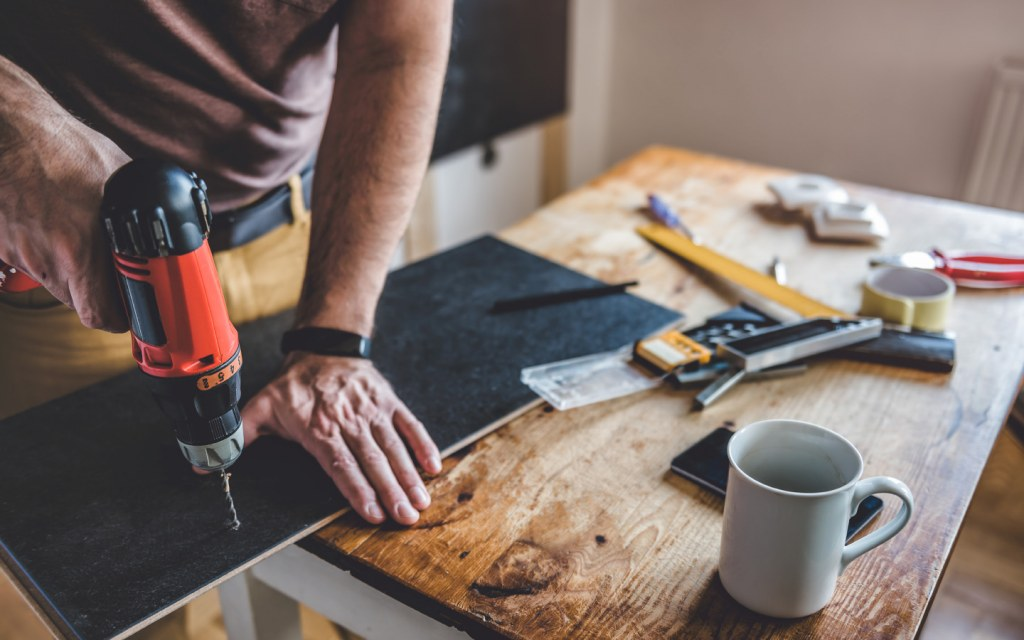 Man using a power drill on laminate board for home renovation
