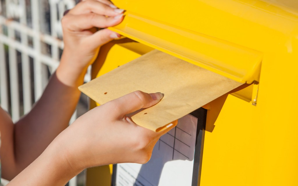 Woman puts envelope in yellow mail box