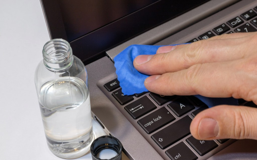 Wiping laptop keyboard with microfiber cloth and cleaning solution