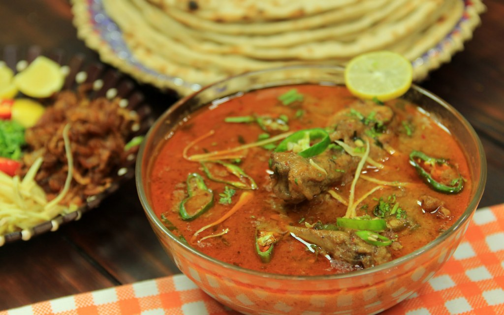 Popular Lahori food Nihari in a dish next to a plate of naan
