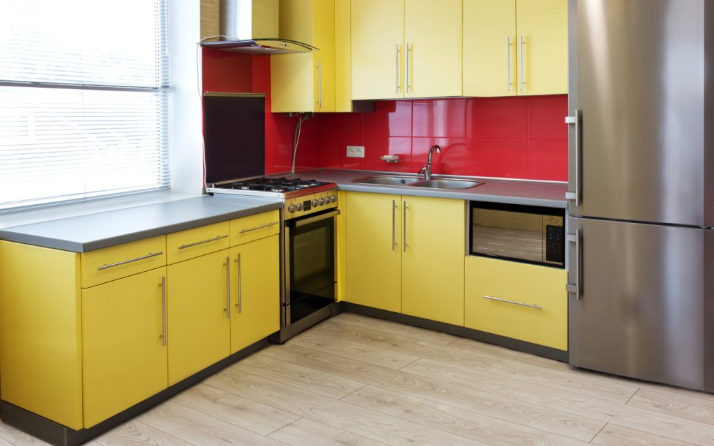 Kitchen with yellow cabinets and red backsplash