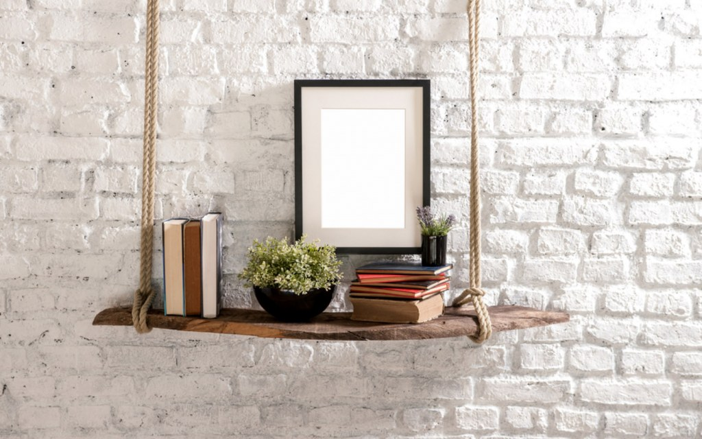Hanging bookshelf with photo frame against bricked wall