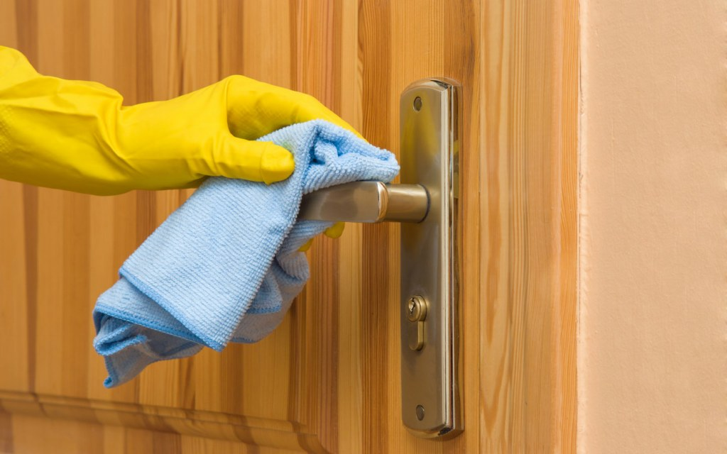 Person cleaning knob on wooden door with a cloth