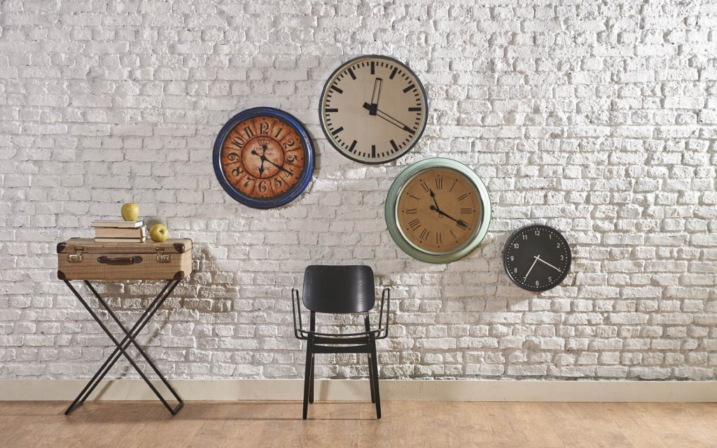Clock collection on white bricked wall