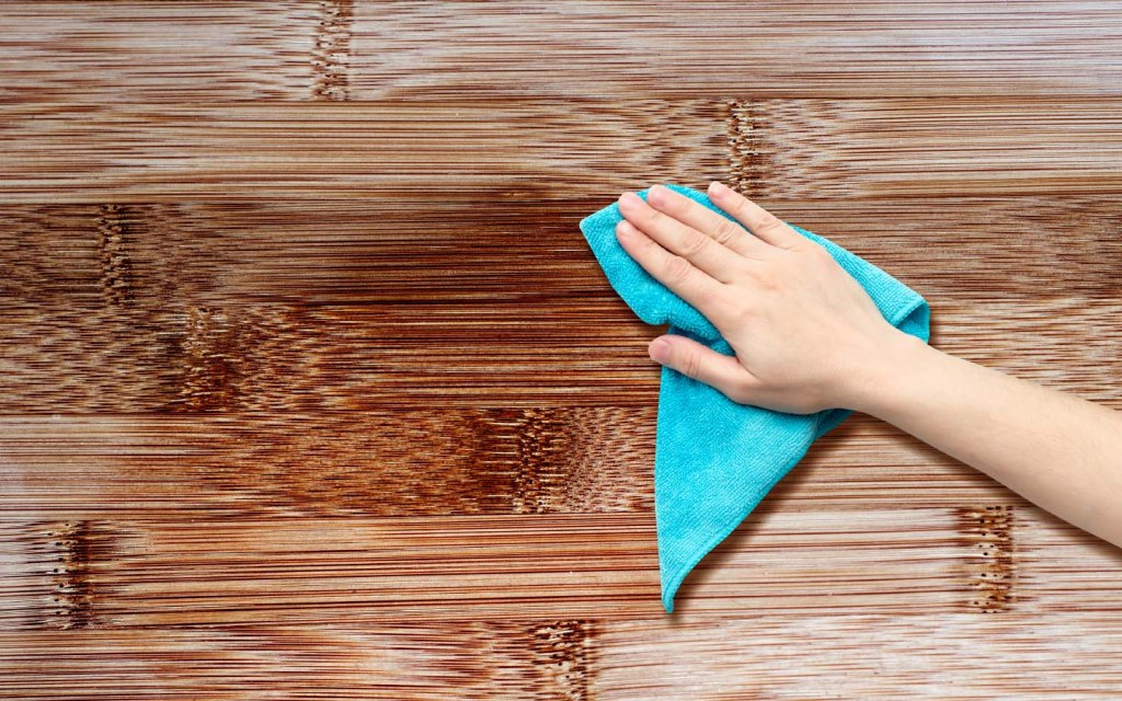 Person cleaning wooden surface with a rag