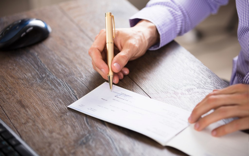 Man signing cheque with a pen