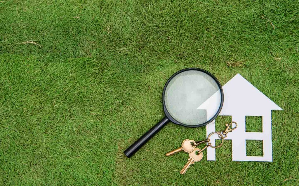 A magnifying glass with a model house