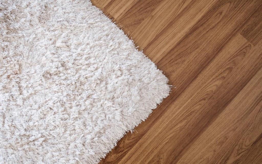 Fluffy white rug on wooden floor