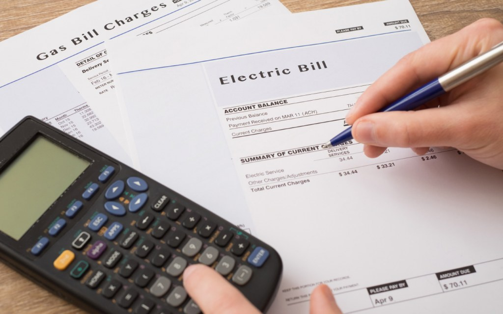Person using calculator for electric bill charges