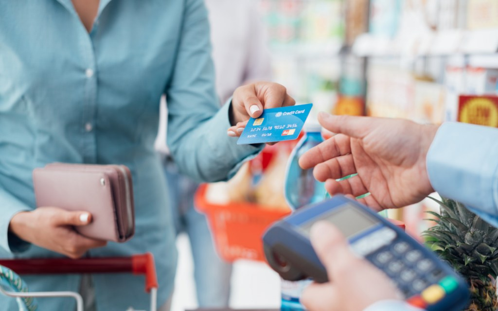 Woman pays with her credit card at checkout counter