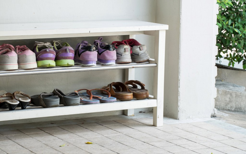 Shoe shelf places outside house with different types of shoes