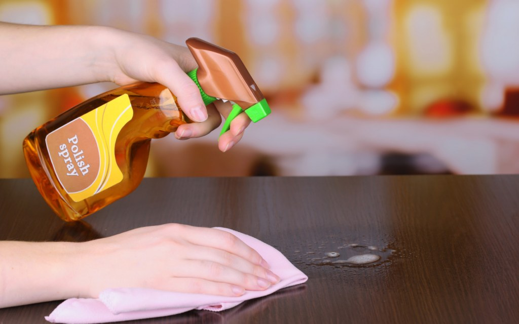 Person cleans wooden table with a cloth and polish spray