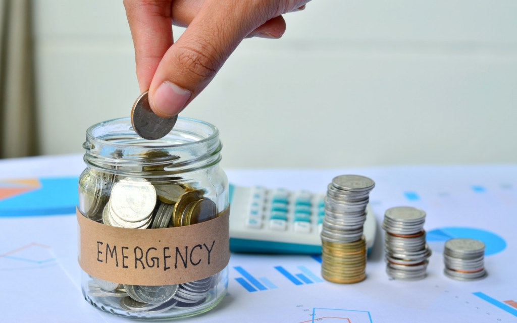 A glass jar labelled 'Emergency' and a hand adding coins to it
