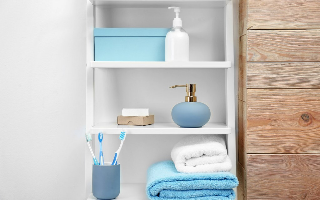 Towels, toiletries and soap dispenser sit on open shelves in a bathroom