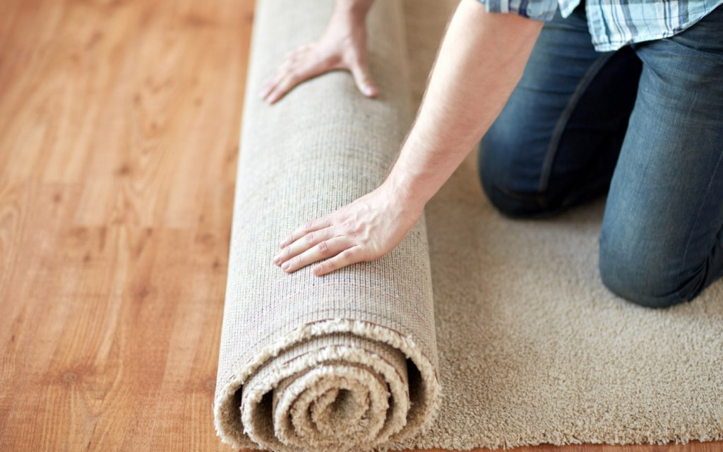 Man rolling carpet to get rid of dust allergens