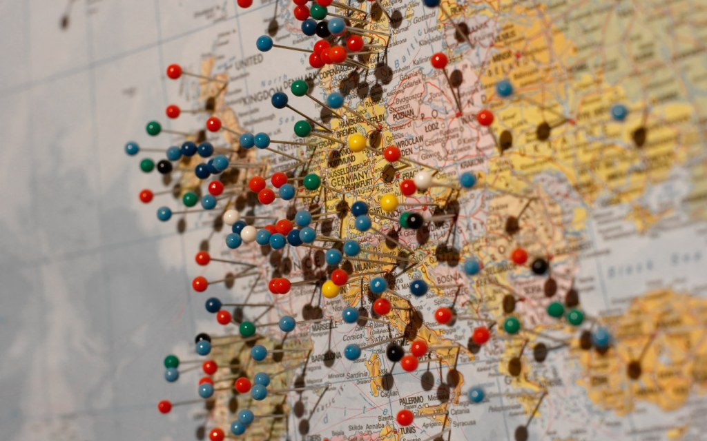 World map with thumbtacks pinned to it