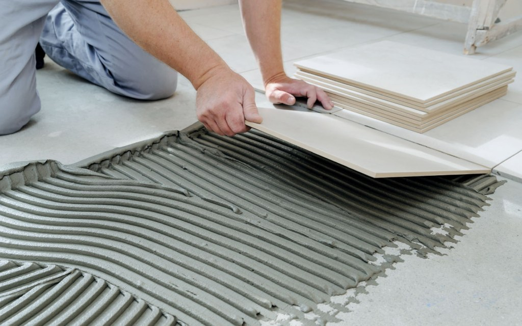 Person laying ceramic tile on floor