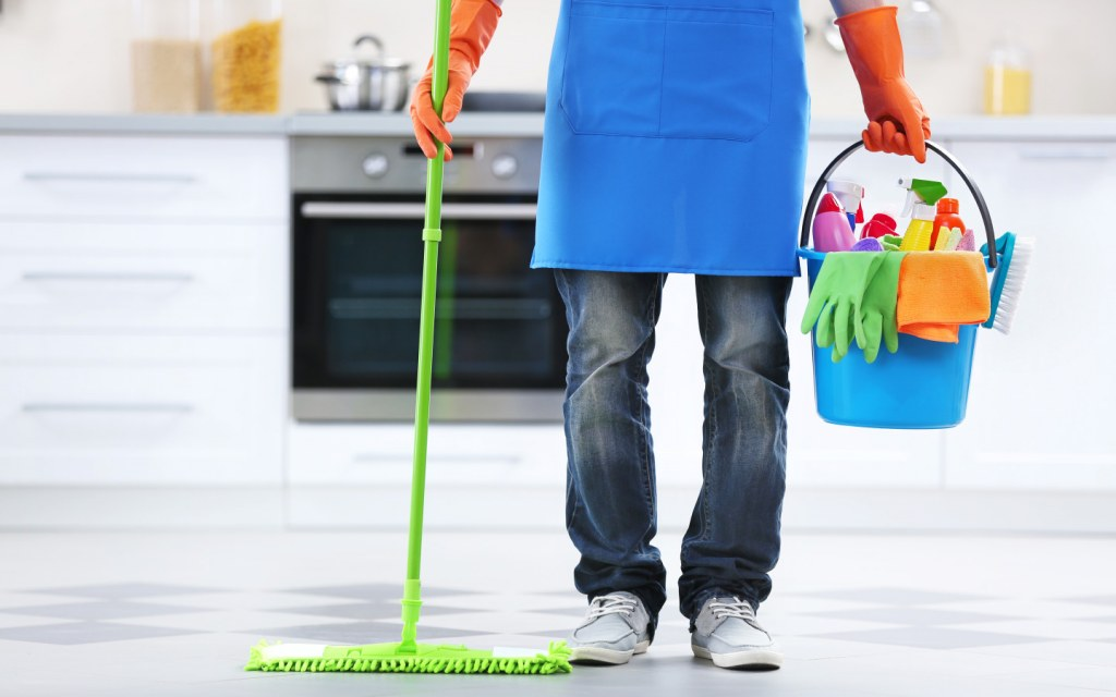 Man holding mop and plastic bucket with cleaning products in kitchen