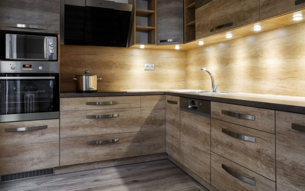 Brown kitchen with LED strip lights under the top cabinets
