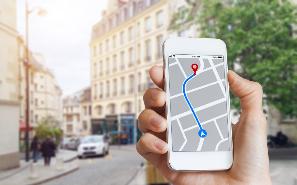 Tourist using GPS map navigation app on smartphone to get directions