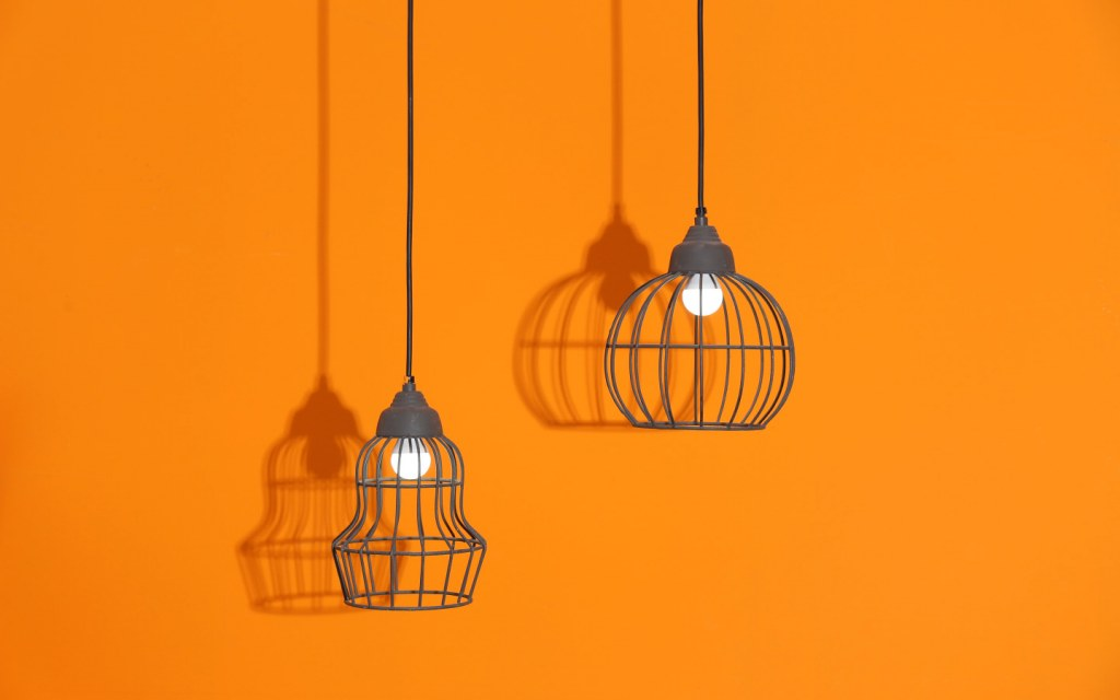 Two pendant lights hanging in front of an orange wall