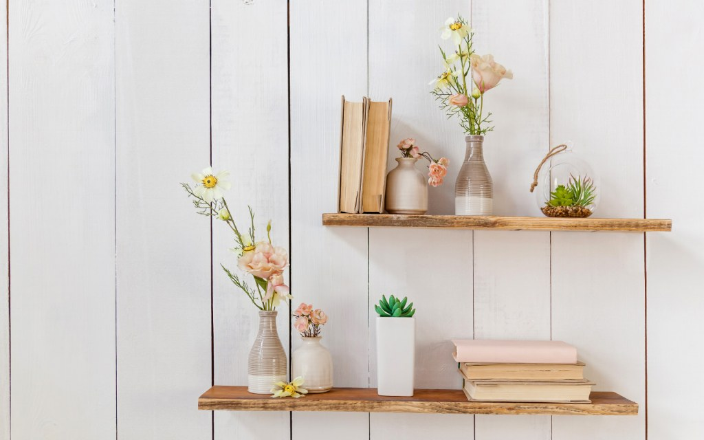 Books and flowers in a vase on floating wooden bookshelf