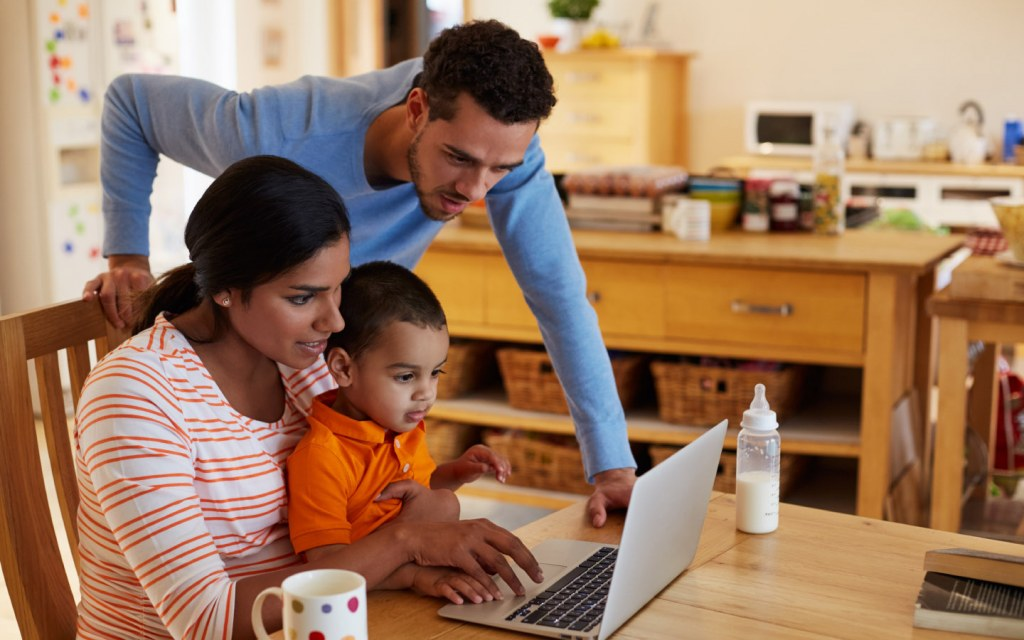 Family looks at laptop together in a kitchen