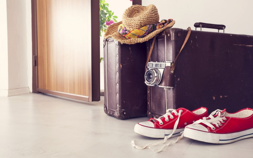 Vacation suitcases and sneakers by front door