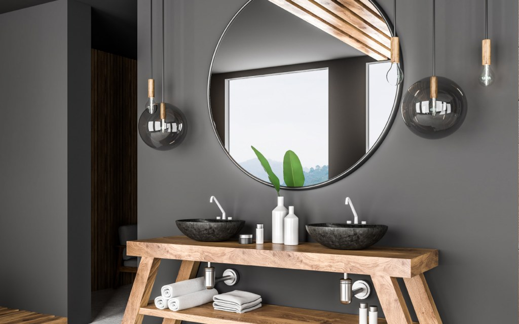 A big round mirror hangs above double bathroom sink