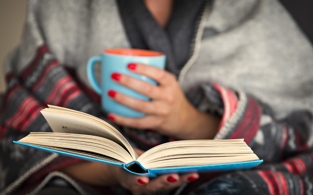 Woman reading a book while holding a mug of hot beverage