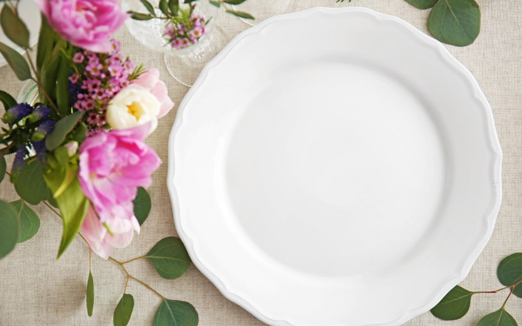 White plate on a table surrounded by floral arrangement