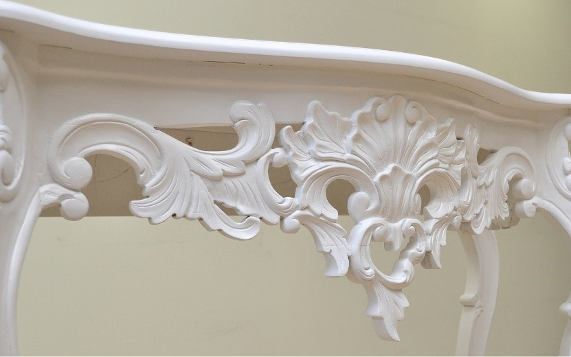A white wooden table with intricate carvings