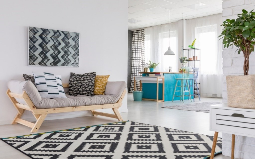 A black and white geometric painting hangs near geometric pillows and area rug