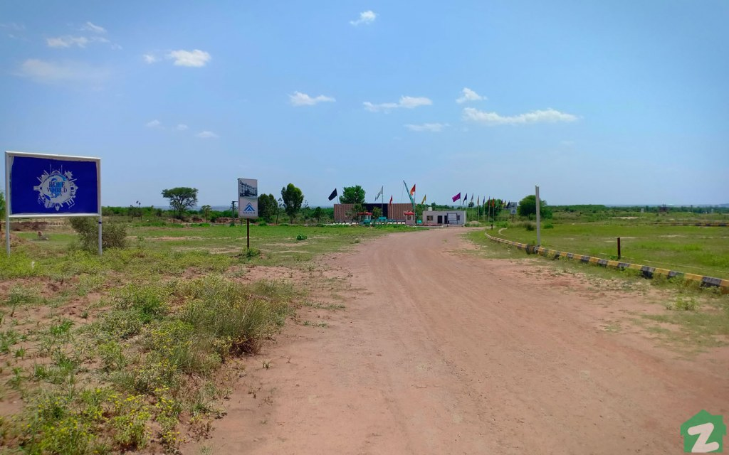 A road with plots on both sides in Blue World City