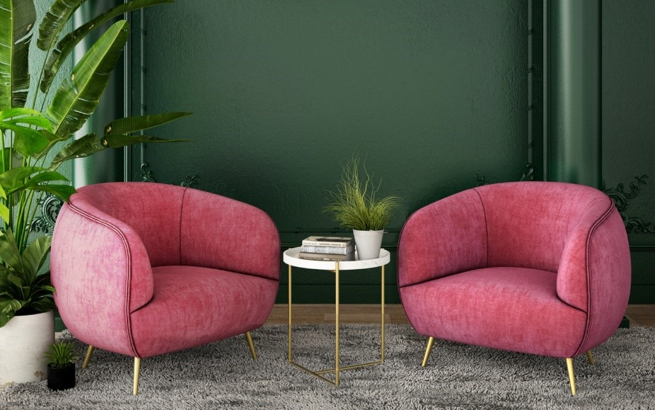 Two bright pink sofas sit in front of a forest green wall