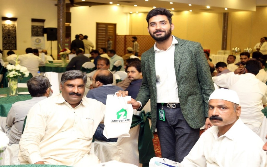 An attendee receives a giveaway at the Faisalabad event